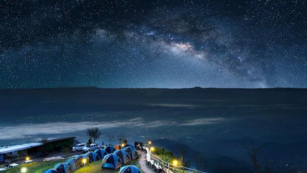 Céu estrelado à noite no alto das montanhas e uma tenda