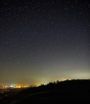 Céu estrelado à noite sobre a cidade e a floresta. paisagem com longa exposição.