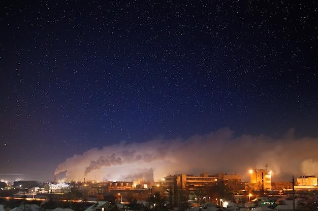 Céu estrelado à noite sobre uma área industrial da cidade