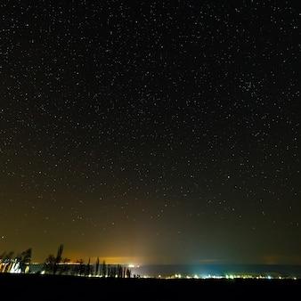Céu estrelado acima da cidade iluminada.