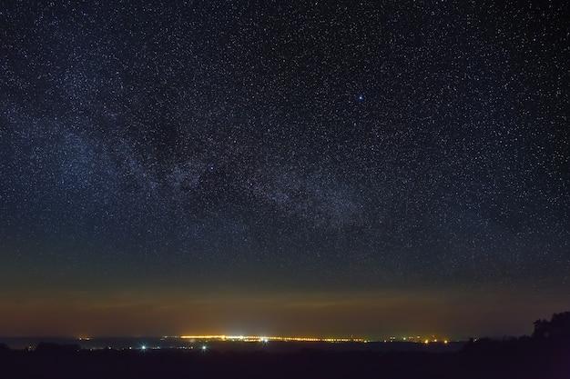 Céu estrelado com a via láctea sobre a cidade com iluminação