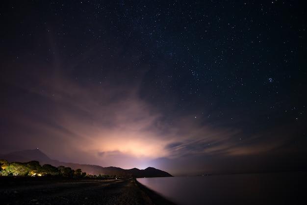 Céu estrelado da noite na costa do mar