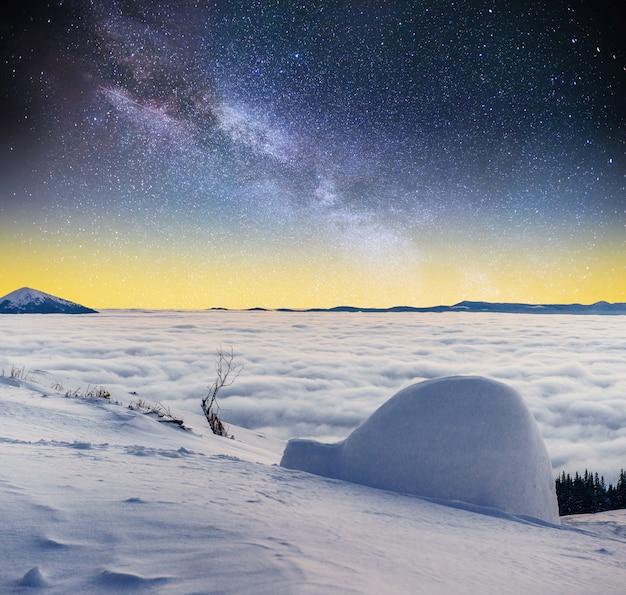 Céu estrelado e a via láctea, um yurt nas montanhas de nevoeiro do inverno