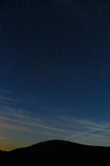 Céu estrelado em um fundo de picos de montanha.