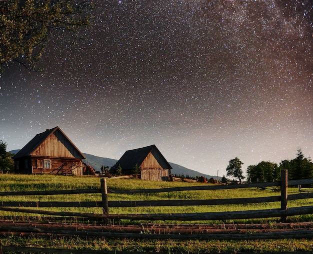 Céu estrelado fantástico pilhas e aldeias de montanha tradicionais. cárpatos, ucrânia