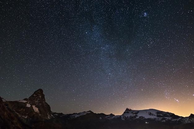 Céu estrelado maravilhoso sobre o pico de montanha de matterhorn (cervino) e as geleiras de monte rosa.