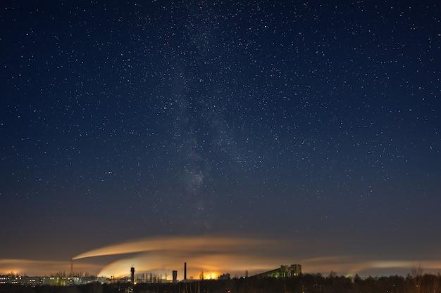 Céu estrelado noturno com a via láctea sobre a área industrial da cidade. paisagem fotografada no inverno na rússia.