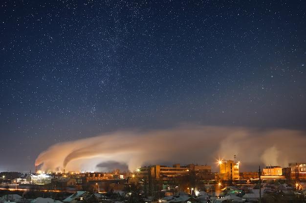 Céu estrelado noturno sobre uma área industrial da cidade paisagem no inverno na rússia