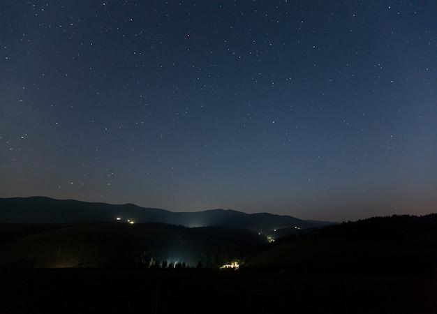 Céu estrelado sobre as montanhas e a aldeia de montanha na noite de verão.