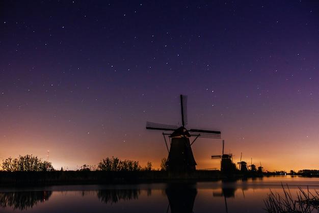Céu estrelado sobre moinhos holandeses.