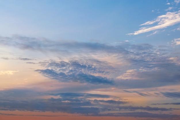 Céu laranja-azul do pôr do sol com nuvens.