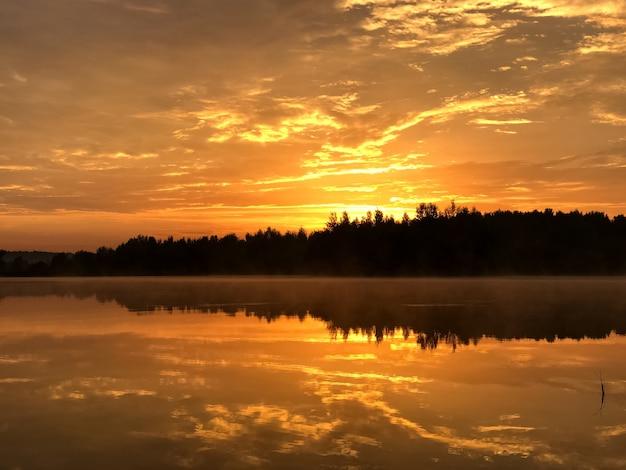 Céu laranja dramático ao pôr do sol sobre o lago da floresta refletindo na superfície da água parada, silhueta da linha da floresta no horizonte