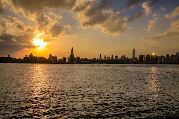 Céu laranja no panorama da cidade de nova york com arranha-céus no horizonte de manhattan