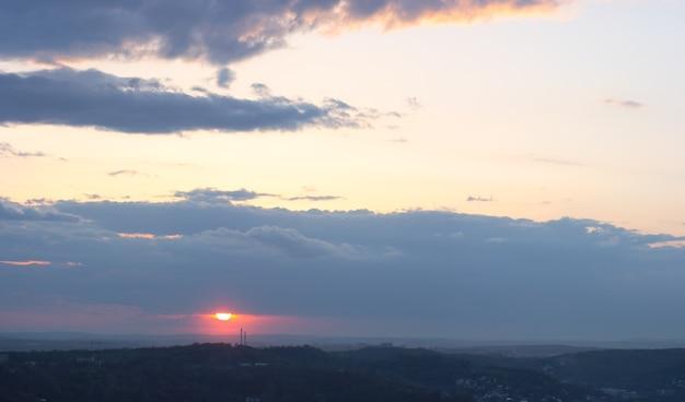 Céu noturno ao pôr do sol com nuvens acima da vista da cidade de lviv