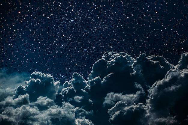 Céu noturno com estrelas e lua e nuvens.