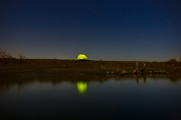 Céu noturno com estrelas sobre a barraca do turista à beira do rio. a paisagem foi fotografada em uma longa exposição.