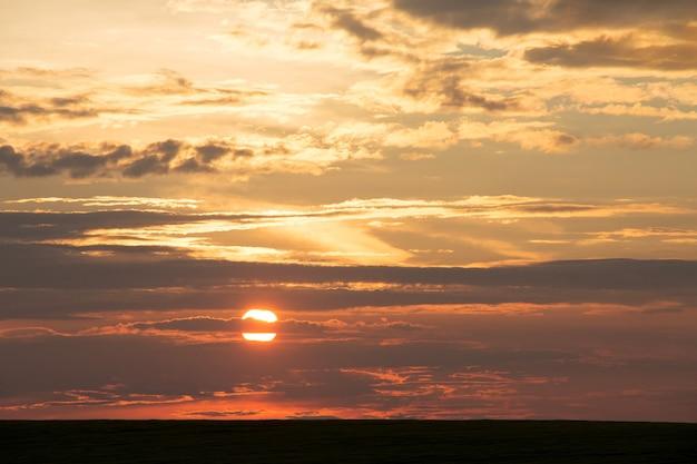 Céu noturno com sol e nuvens pitorescas em cores quentes