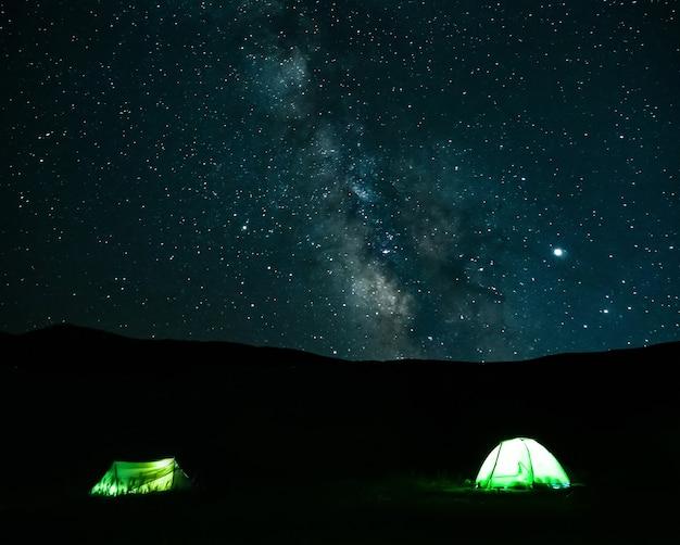 Céu noturno com via láctea e tendas de acampamento leves