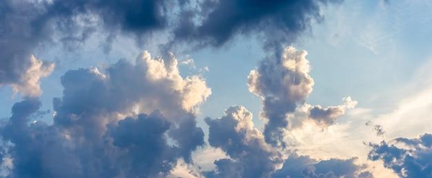 Céu noturno dramático com nuvens claras e escuras iluminadas pelo sol