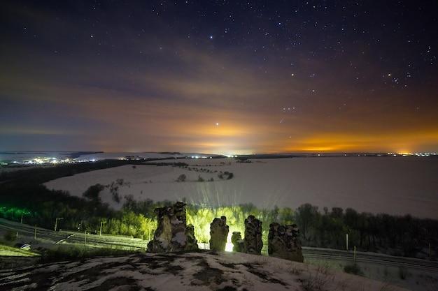 Céu noturno estrelado e brilhante acima da paisagem de neve