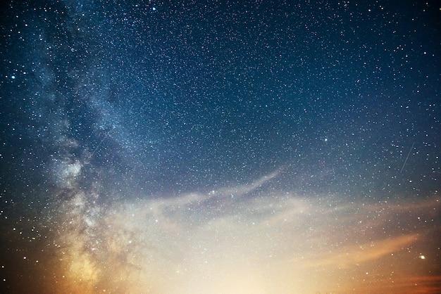 Céu noturno vibrante com estrelas, nebulosa e galáxia.