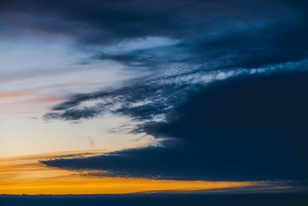 Céu nublado azul dramático surpreendente com luz do sol alaranjada nas nuvens. fundo atmosférico em tempo nublado. aviso de tempestade. cloudscape escuro lindo. pôr do sol. nascer do sol. alvorecer. copie o espaço.