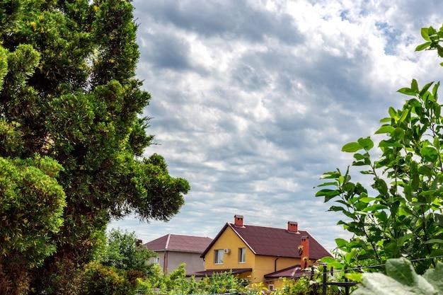 Céu nublado. construção de casa de madeira, campo verde com a casa no dia nublado.