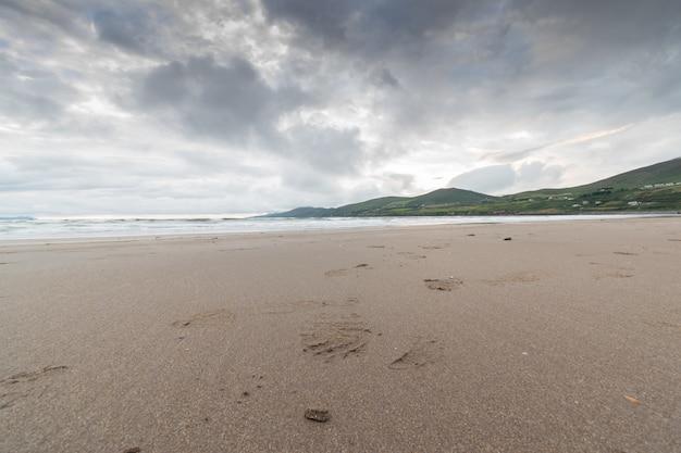 Céu nublado sobre as areias de uma praia com maré vazante. mauntains à distância.