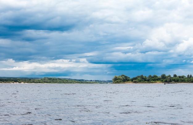 Céu nublado sobre um rio tempestuoso com margens verdes e uma cidade à distância.