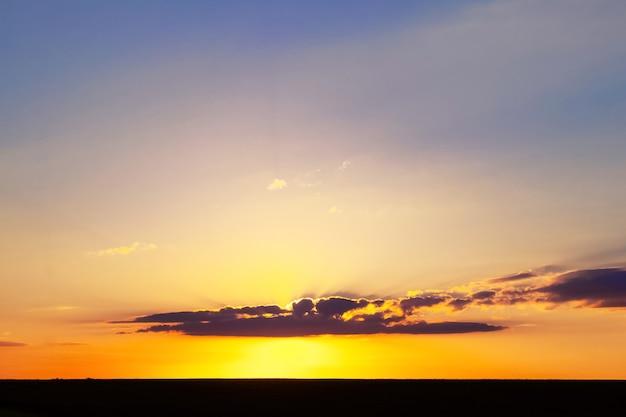 Céu pitoresco ao pôr do sol e uma estreita faixa escura de campo