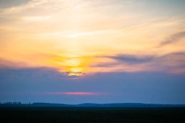 Céu pitoresco com nuvens coloridas ao pôr do sol. campo à noite durante o pôr do sol.