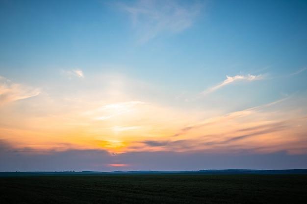 Céu pitoresco e faixa de campo durante o pôr do sol