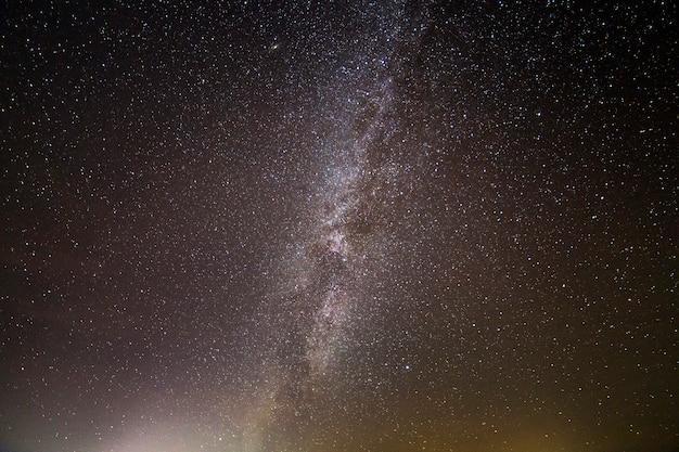 Céu preto escuro com inúmeras estrelas cintilantes brancas brilhantes e galáxia da via láctea. beleza da natureza.