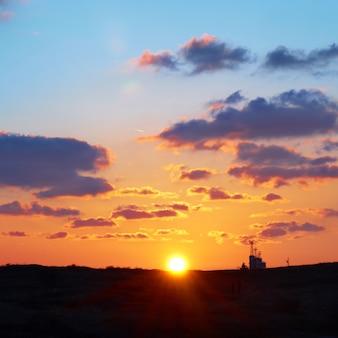 Céu romântico com sol, lindas nuvens vermelhas e amarelas