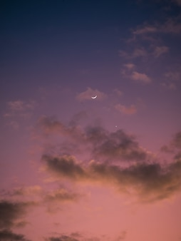 Céu rosa e roxo com lua e estrela no pôr do sol
