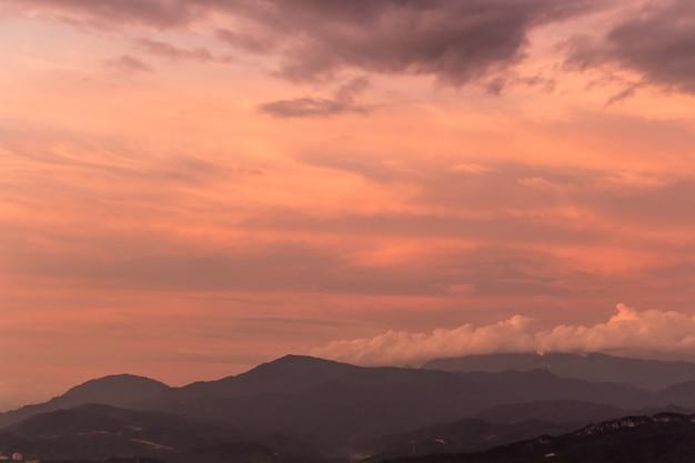 Céu roxo dramático sobre colinas enevoadas