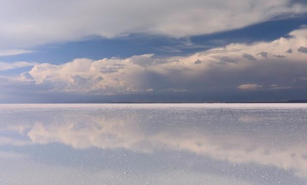 Céu tempestuoso e reflexões de nuvens em águas rasas de salar de uyuni, bolívia