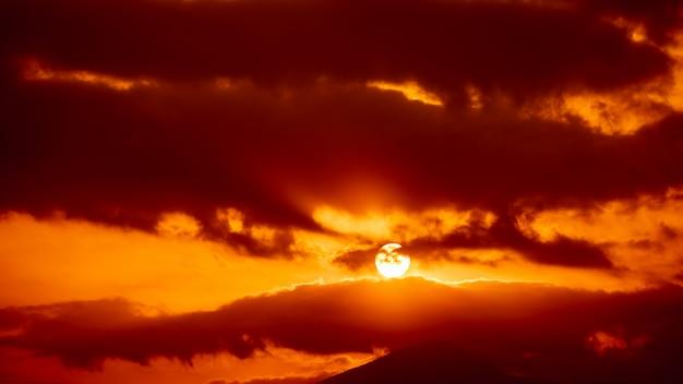 Céu vermelho e sobre o abstrato do sol com a montanha de silhueta