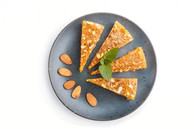 Cezerye turco tradicional dos doces feito do melão caramelizado, nozes torradas, avelã, pistache na placa cerâmica azul isolada no branco. vista do topo