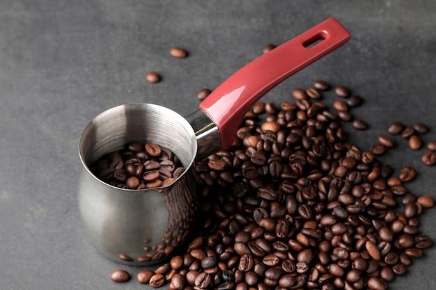 Cezve. com grãos de café torrados em um fundo escuro. fazendo café.