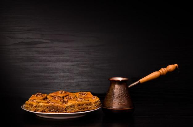 Cezve de café e um prato de baklava com mel no preto