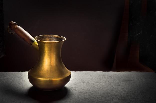 Cezve de cobre velho na ardósia preta