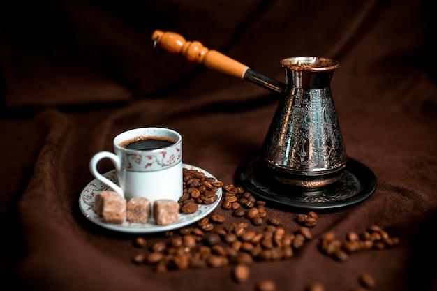 Cezve de prata e grãos de café sobre o tecido marrom escuro.
