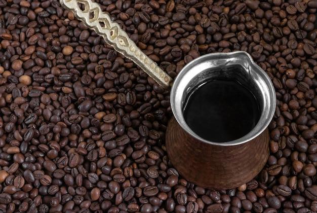 Cezve vintage (café turco) em pé sobre grãos de café