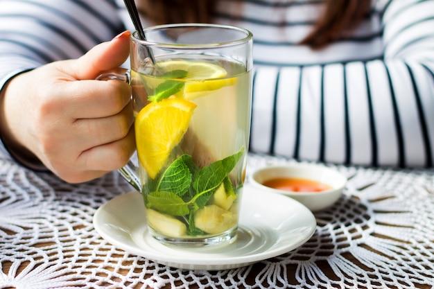 Chá alaranjado da fruta bebendo da menina com hortelã, gengibre e canela.
