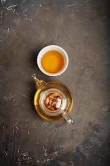 Chá antioxidante e anti-inflamatório saudável com ingredientes frescos gengibre, erva-cidreira, sálvia, mel e limão em fundo escuro com espaço de cópia. vista do topo.