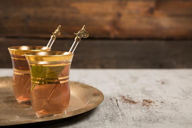 Chá árabe em copos com hortelã verde na bandeja