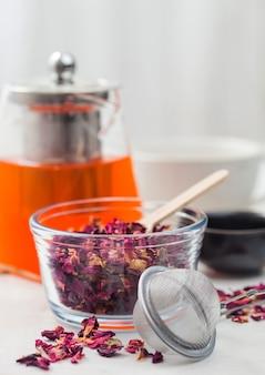 Chá artesanal de pétalas de rosa com infusor de filtro e bule de vidro transparente com xícara de cerâmica branca sobre fundo branco.