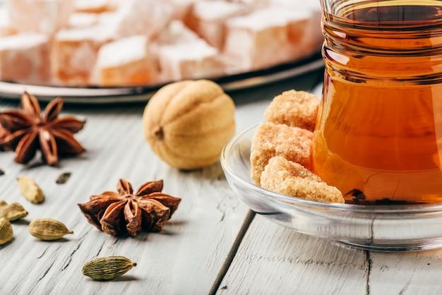 Chá asiático em copo armudu com rahat lokum e especiarias diversas sobre superfície de madeira