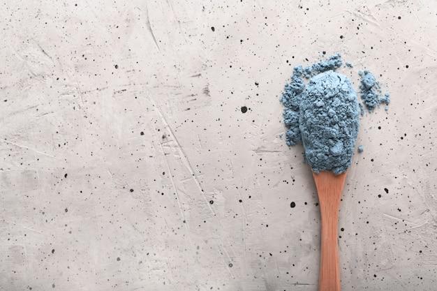Chá azul matcha em uma colher na superfície de concreto, com espaço de cópia